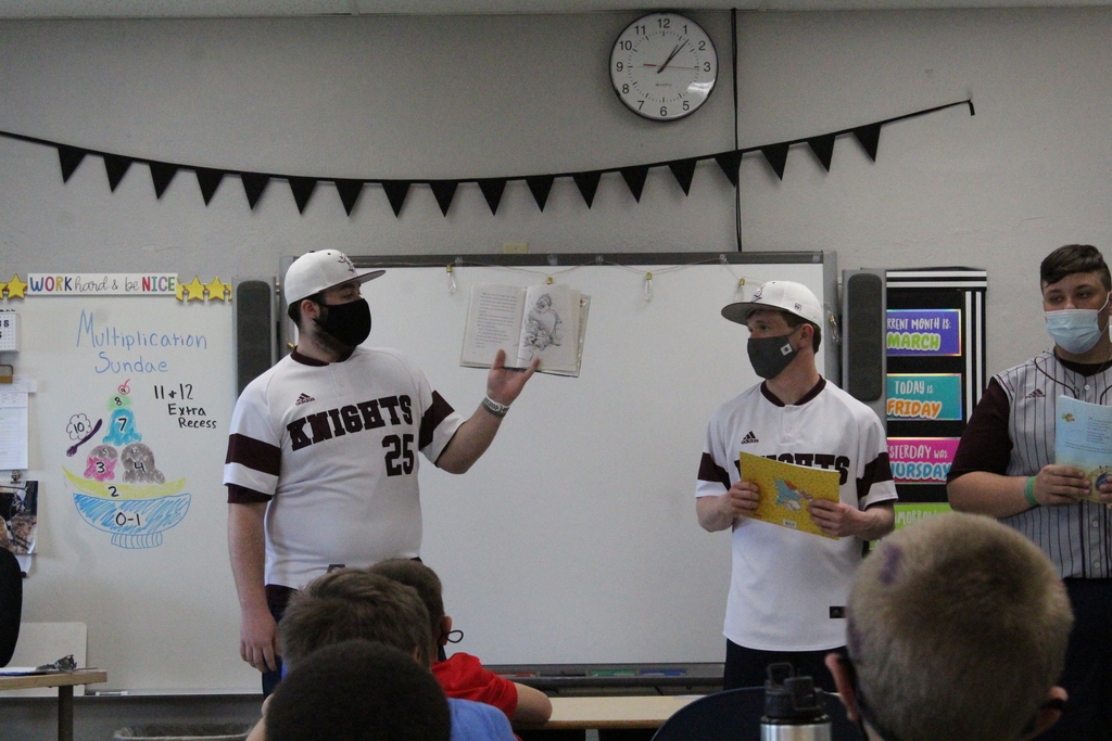 baseball players reading to students